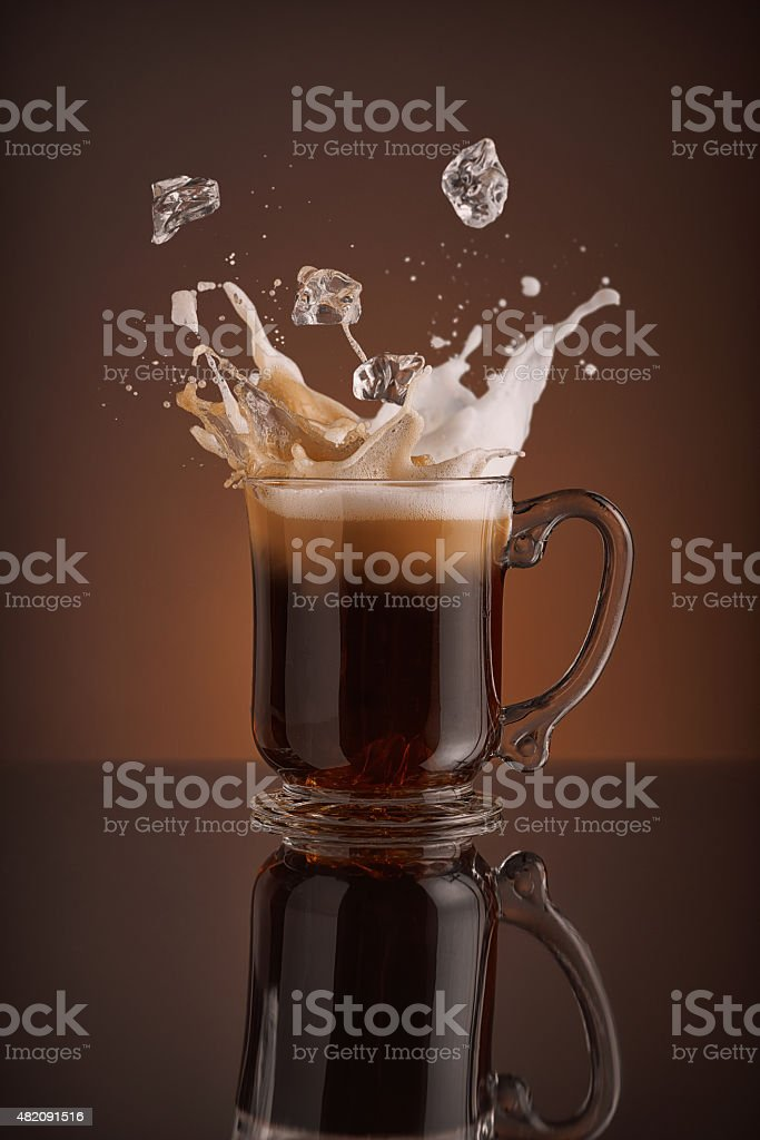 Splash of cappucino coffee on brown background. stock photo