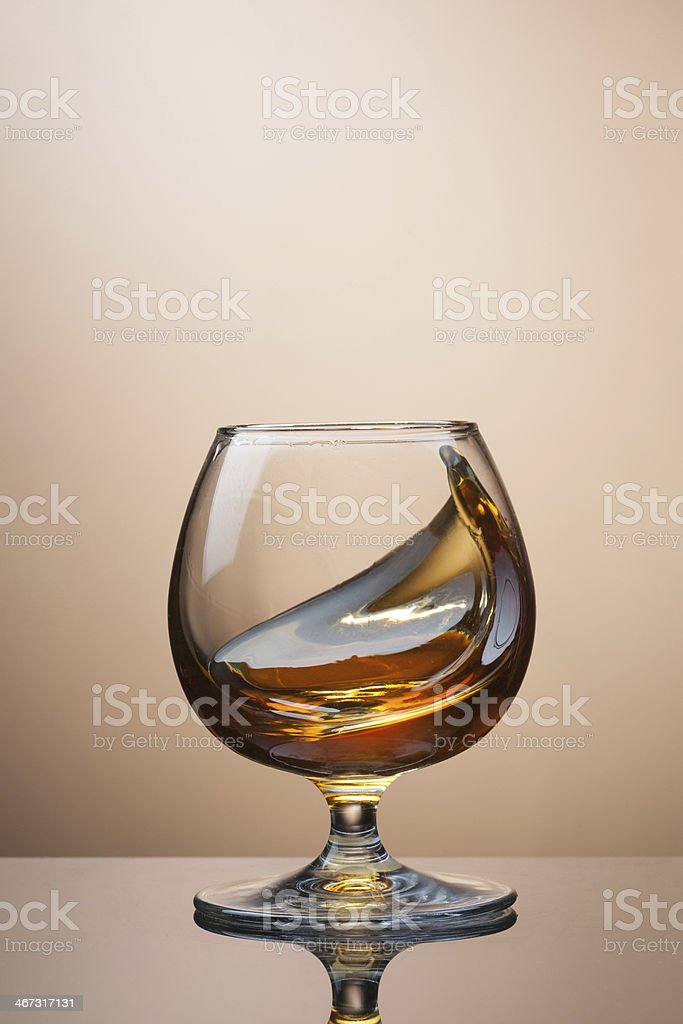 Splash of cognac in glass on brown background stock photo