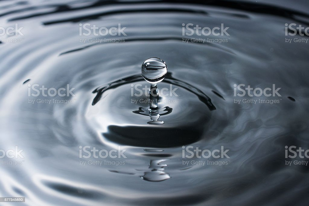 Splash of dark water with droplet from small a drip stock photo