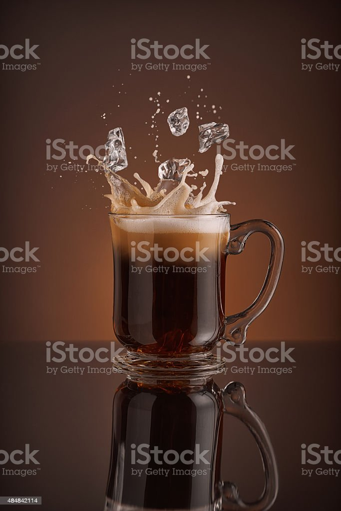 Splash of  ice coffee drink on a brown background. stock photo
