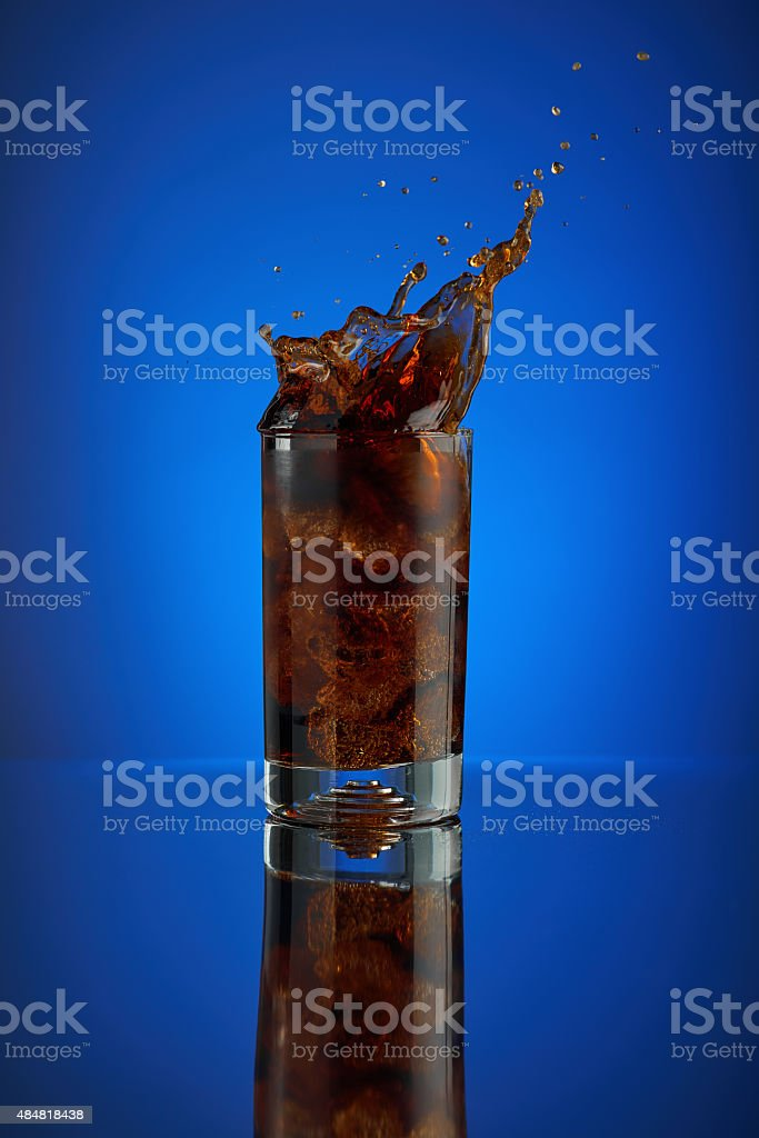 Splash of Pepsi cola soft drink on a blue background. stock photo