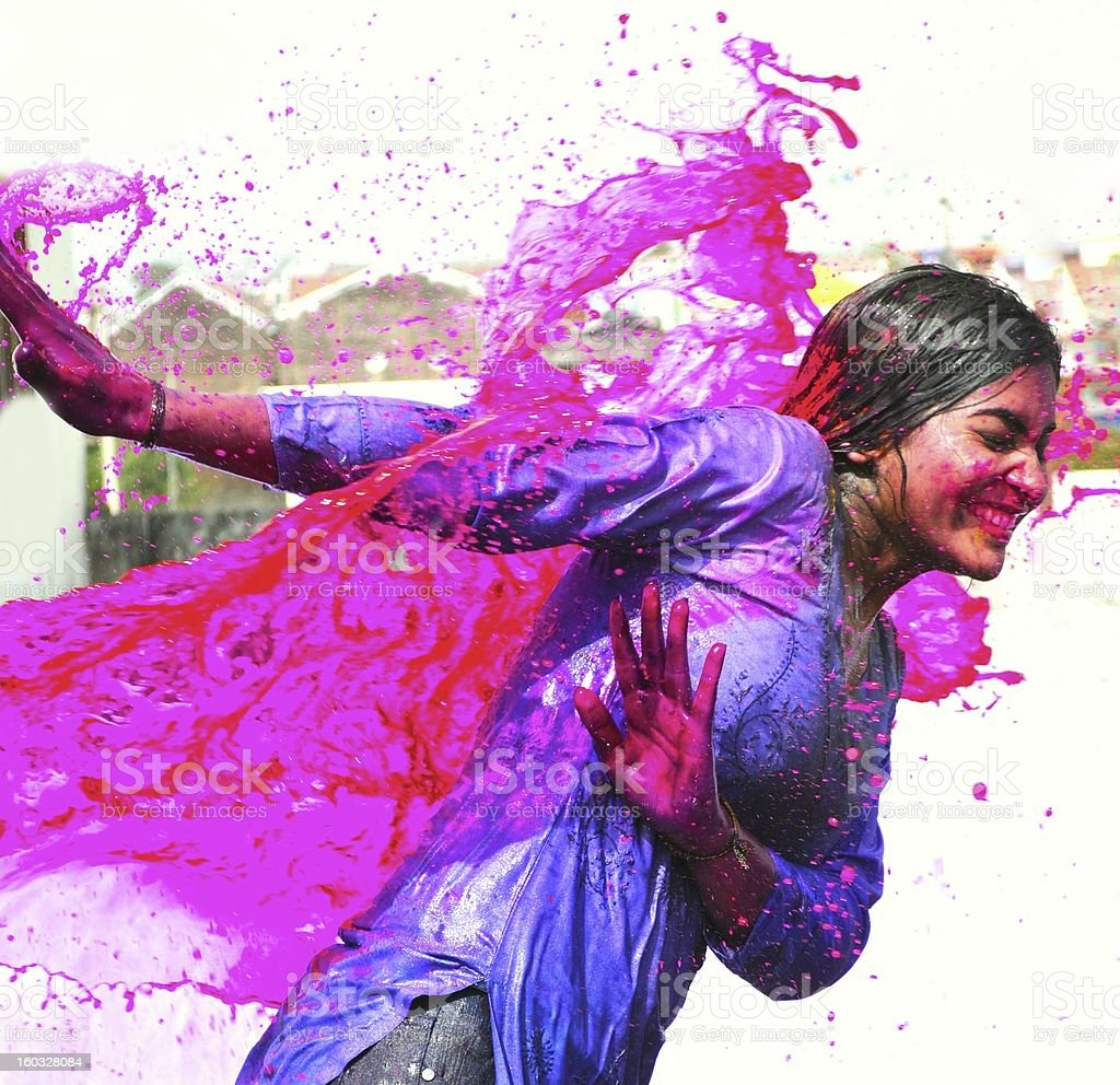 Splash of wet colors on female during Holi celebration. stock photo