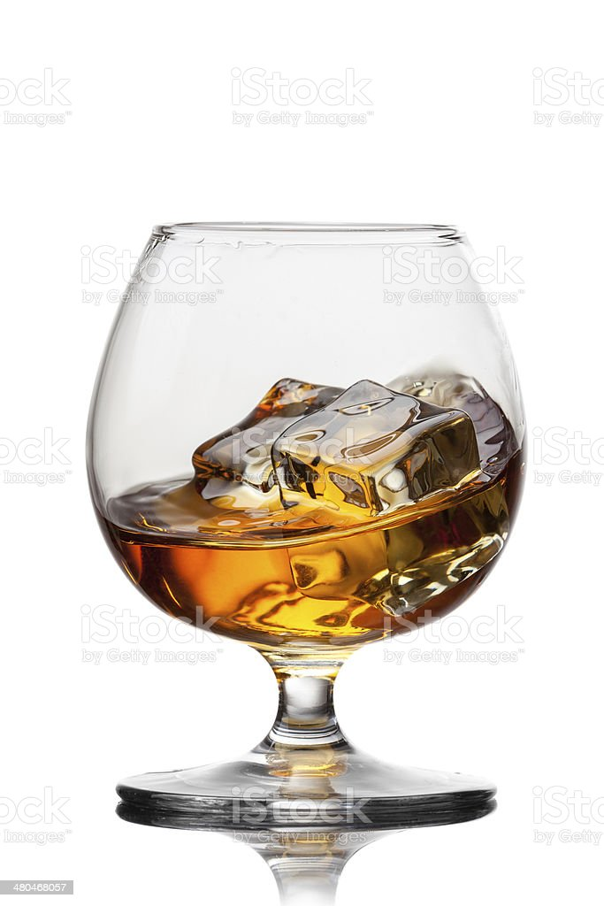 Splash of whiskey with ice in glass isolated on white stock photo