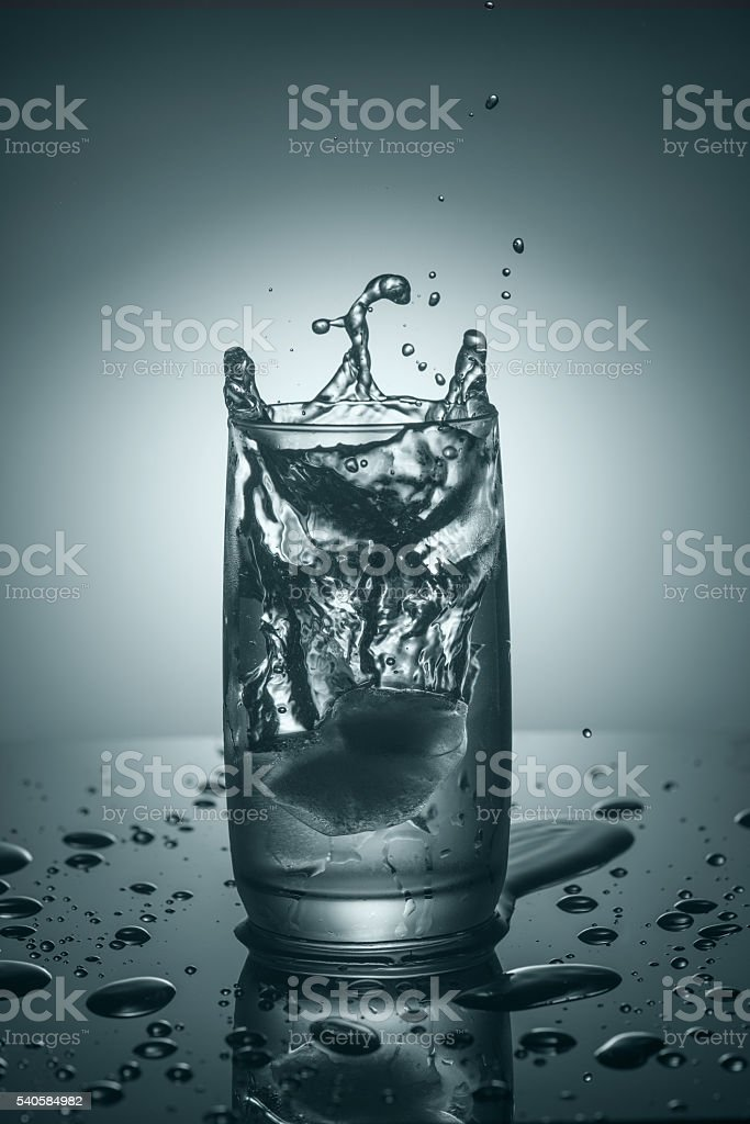 Splashes in a glass of pure cold water stock photo