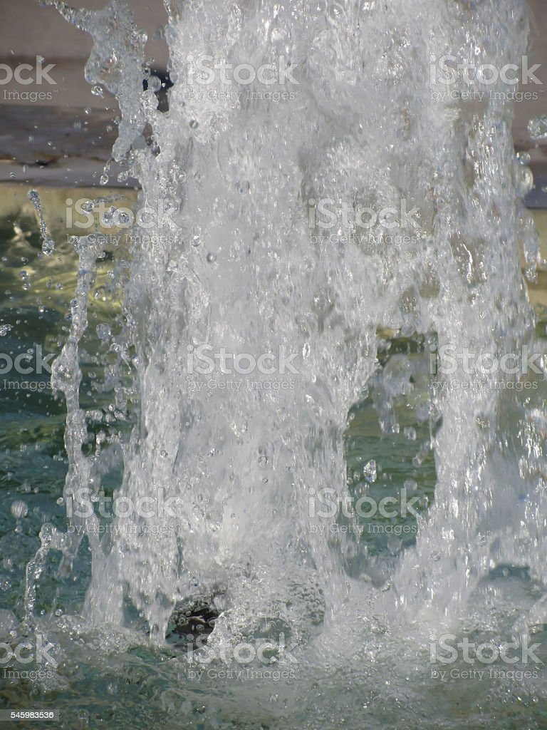 Splashes of fountain water in a sunny day stock photo
