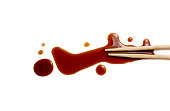 splashes of soy sauce and chopsticks isolated on white