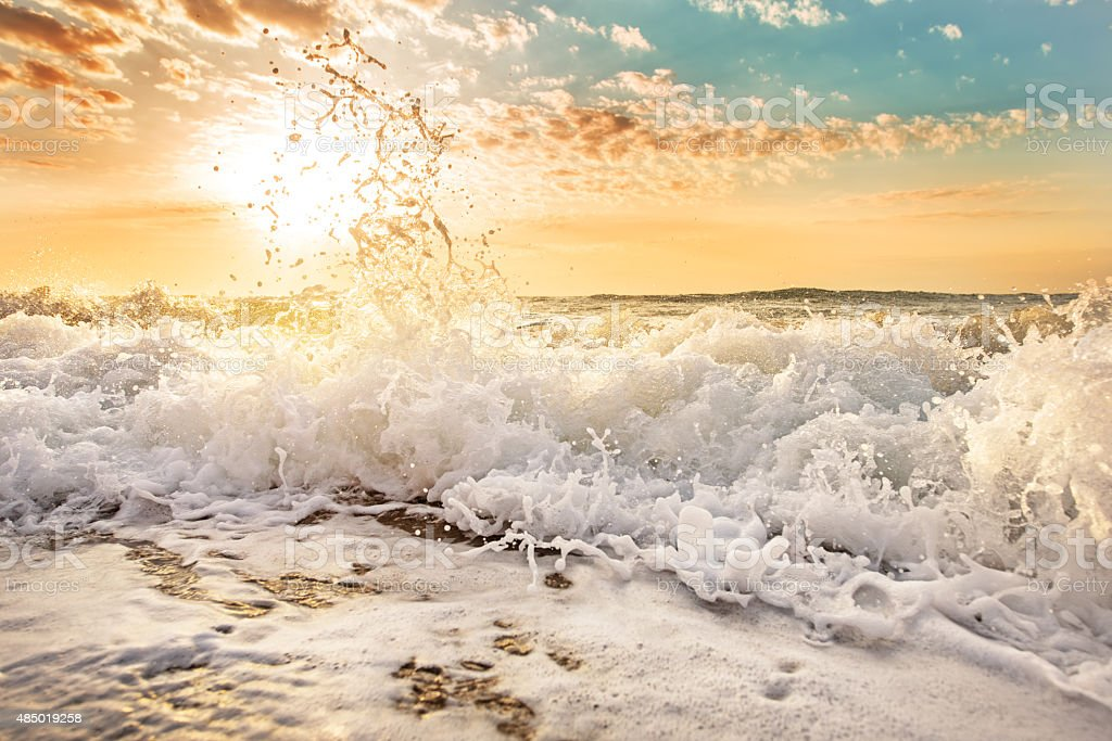 Splashes of wave at sunrise. stock photo