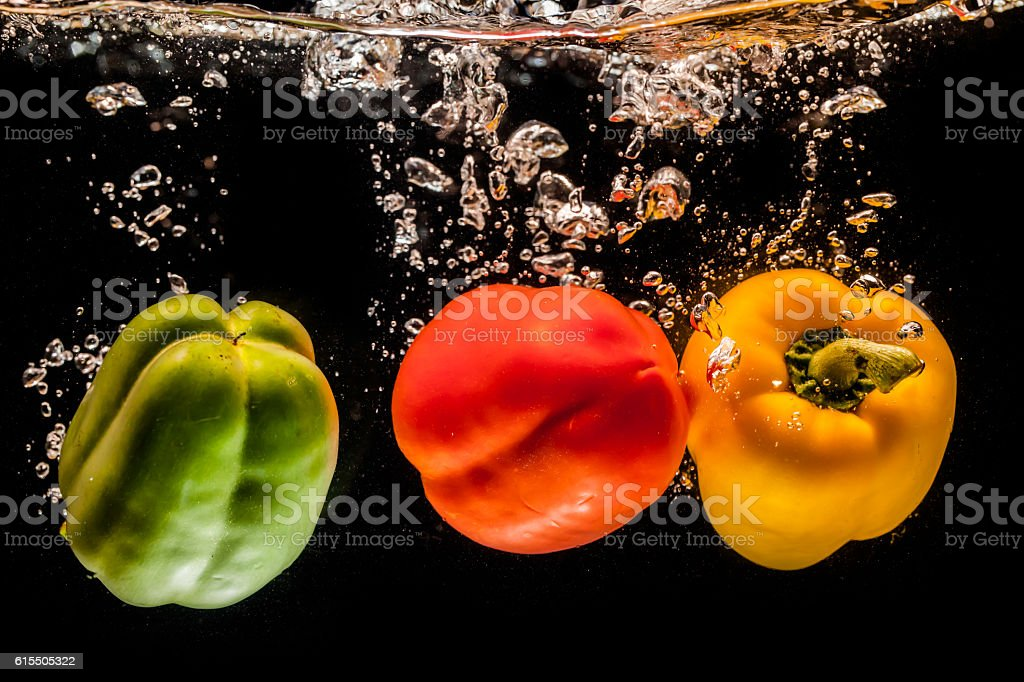 splashing bell peppers on water stock photo