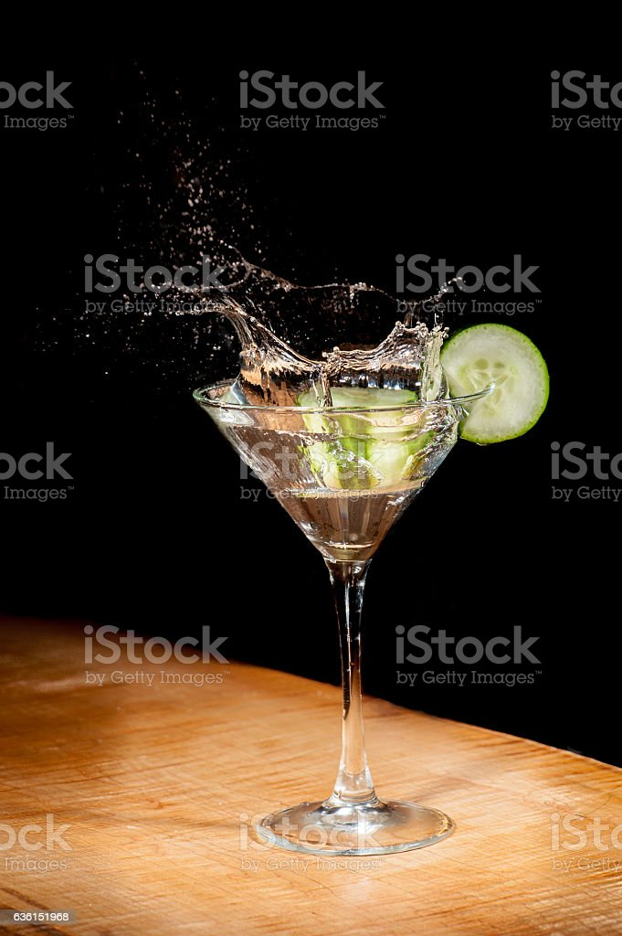 Splashing cocktail with cucumber in martini glass stock photo