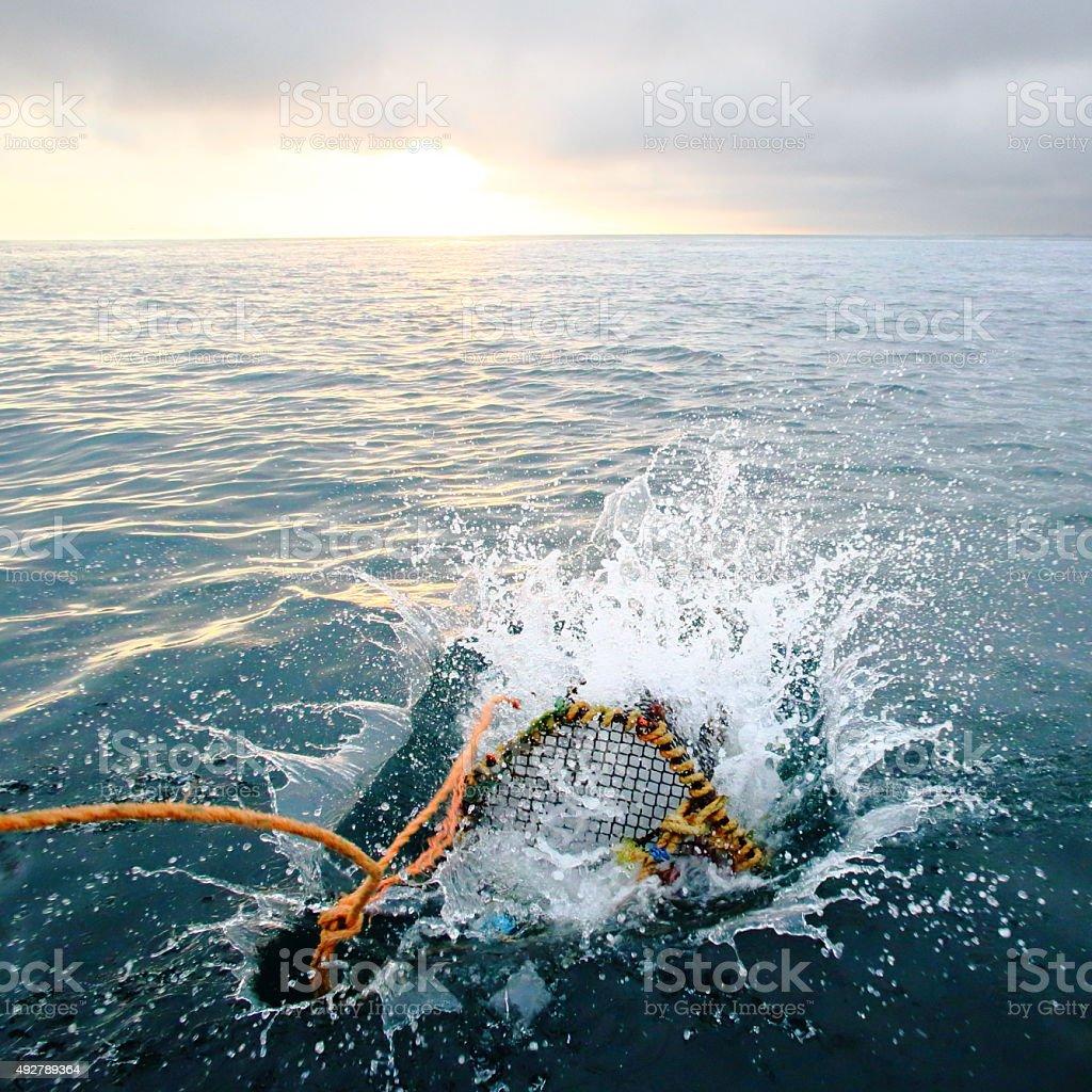 Splashing creel in the sea at dawn stock photo