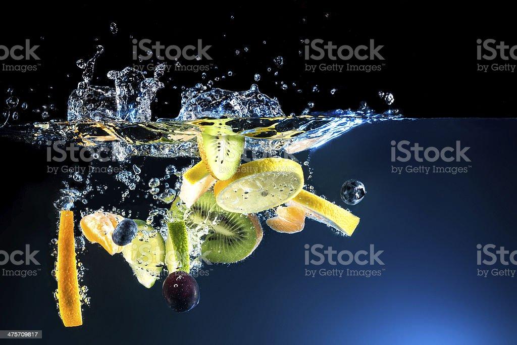 Splashing fresh fruit on water on black background