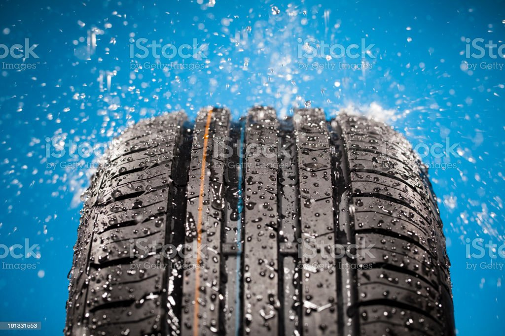 Splashing water on new wet tire against blue background stock photo