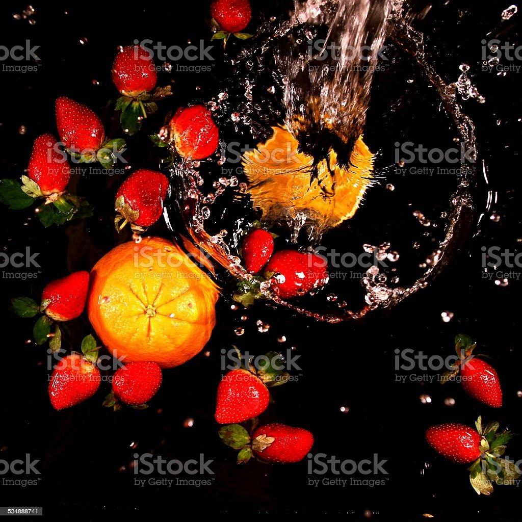 splashing water - Strawberries and cut Orange stock photo