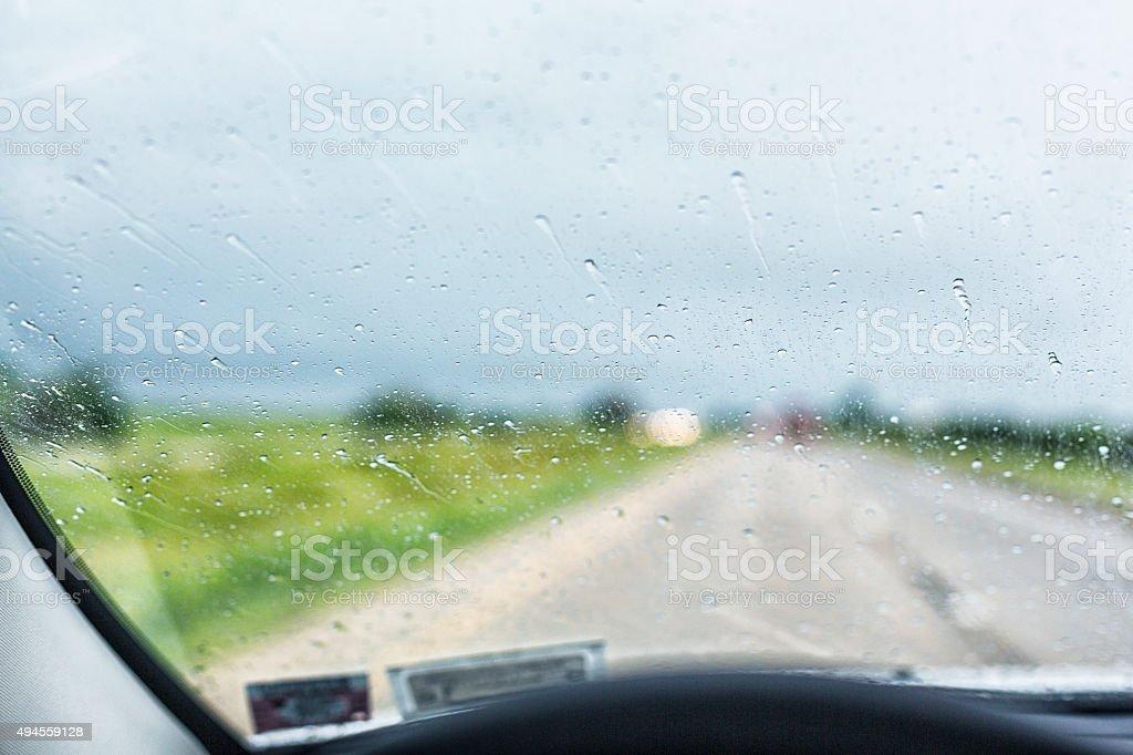 Splattered Rain Storm Raindrops on Speeding Car Blurry Windshield stock photo