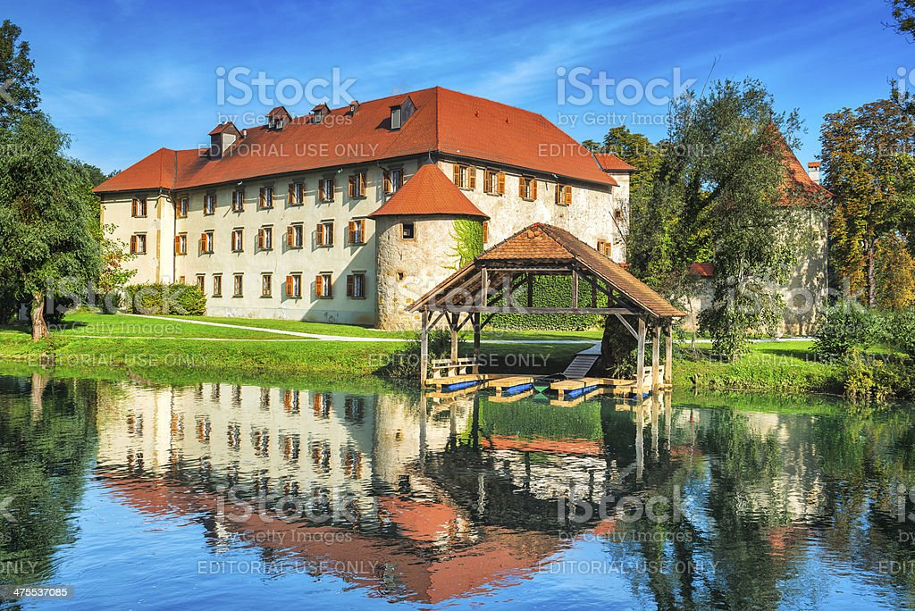 Splendid Castle with Resting Boats by the River, Otocec, Slovenia stock photo