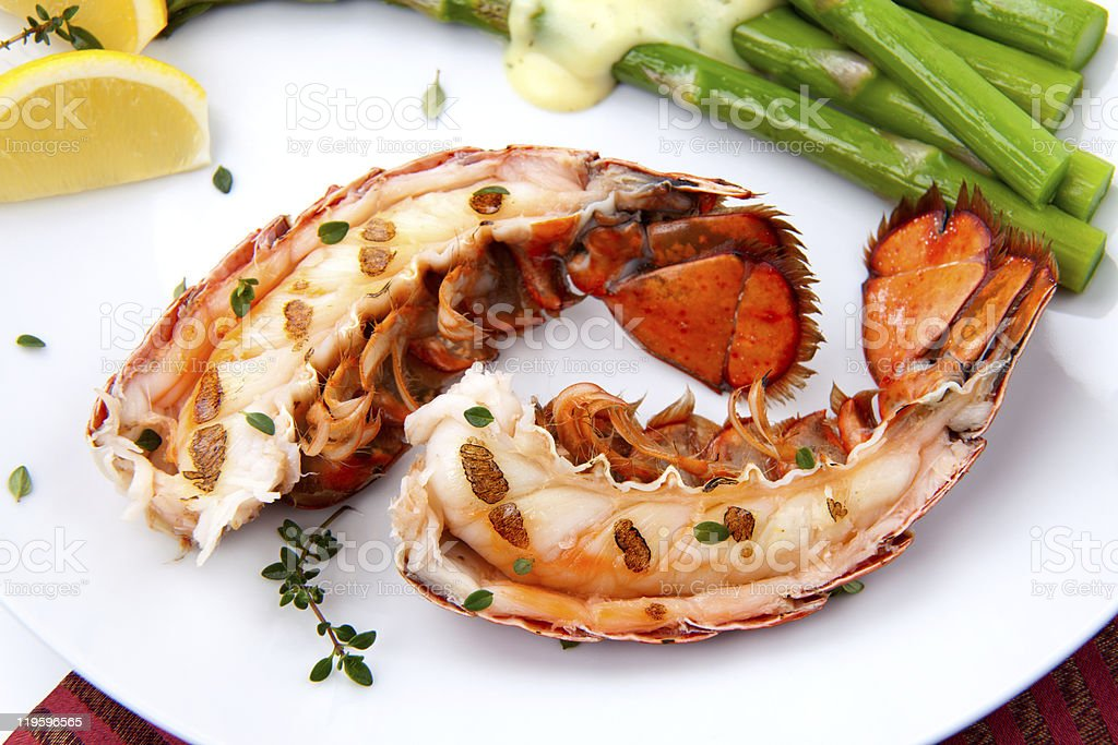 Split garlic roasted lobster tails on a white plate stock photo