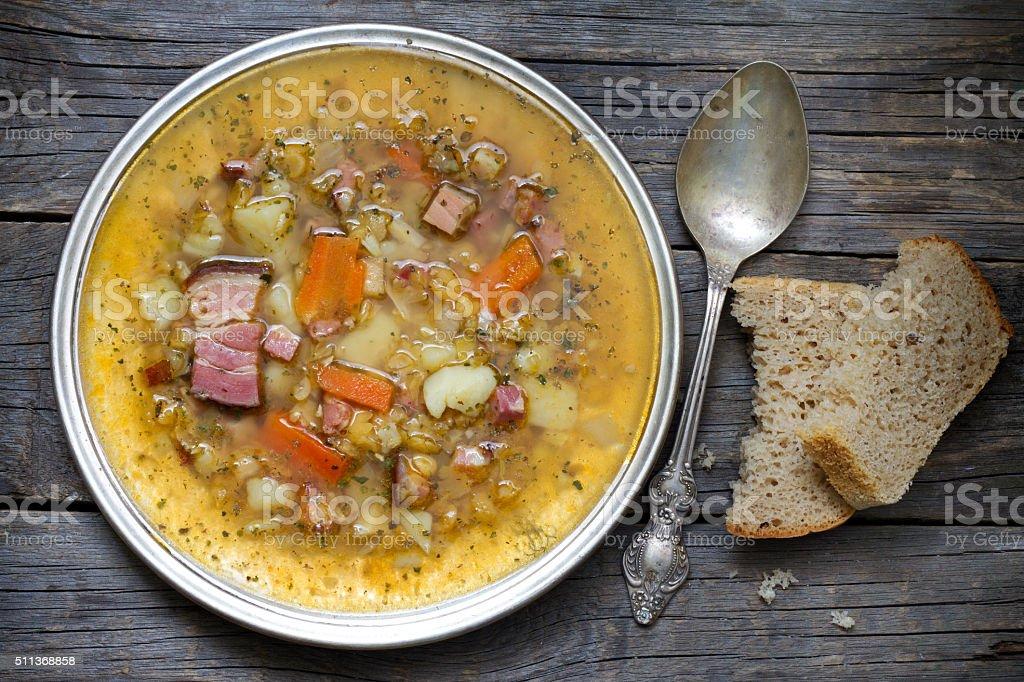 Split pea soup on vintage wooden table stock photo