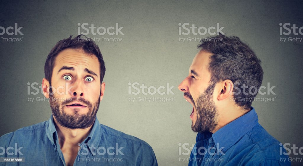 Split personality. Angry man screaming at scared himself stock photo
