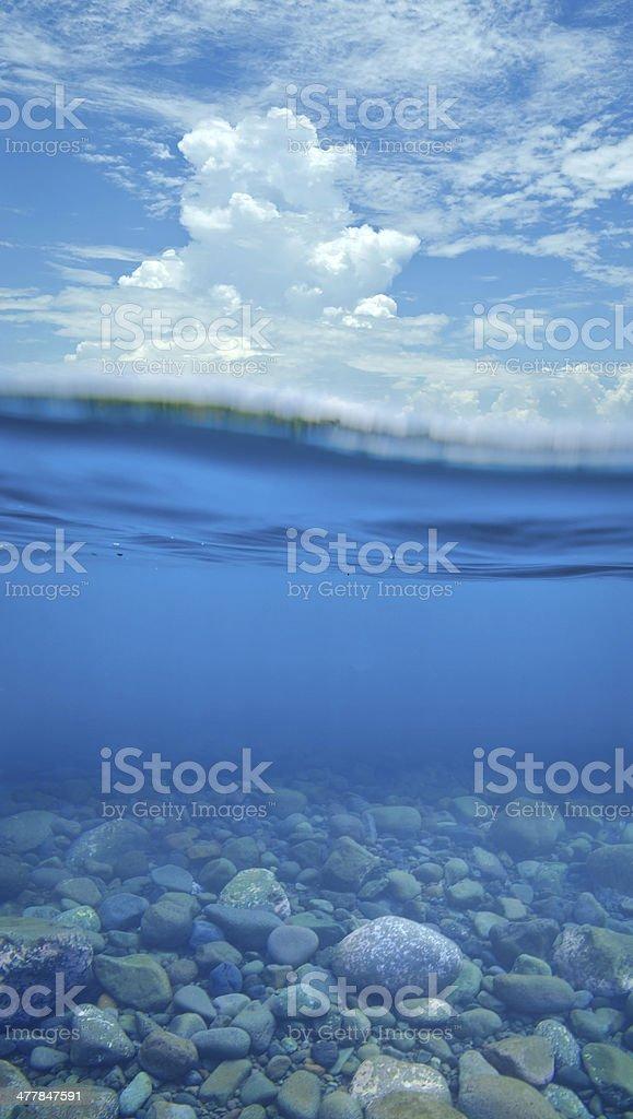 Split shot of ocean with stone underground stock photo