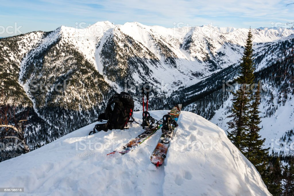 Splitboard, backpack and ski poles on the mountain background stock photo