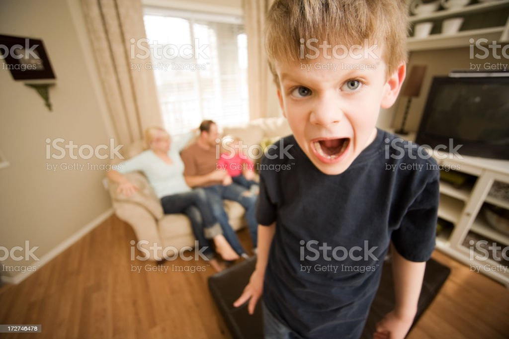Spoiled child screaming at living room stock photo