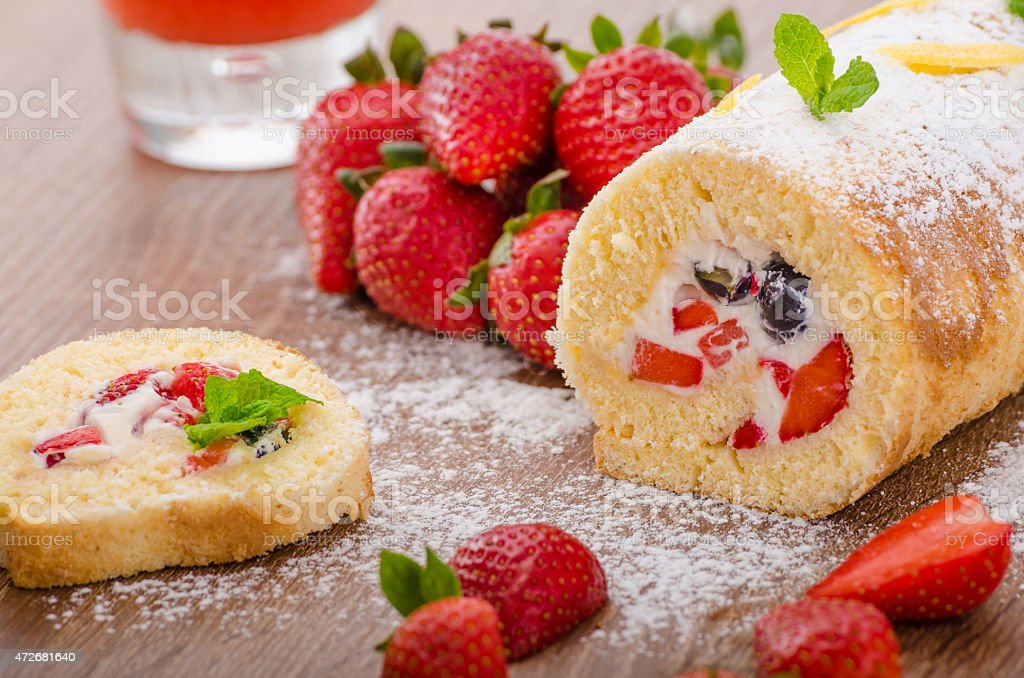 Sponge roll with strawberries and blueberries stock photo