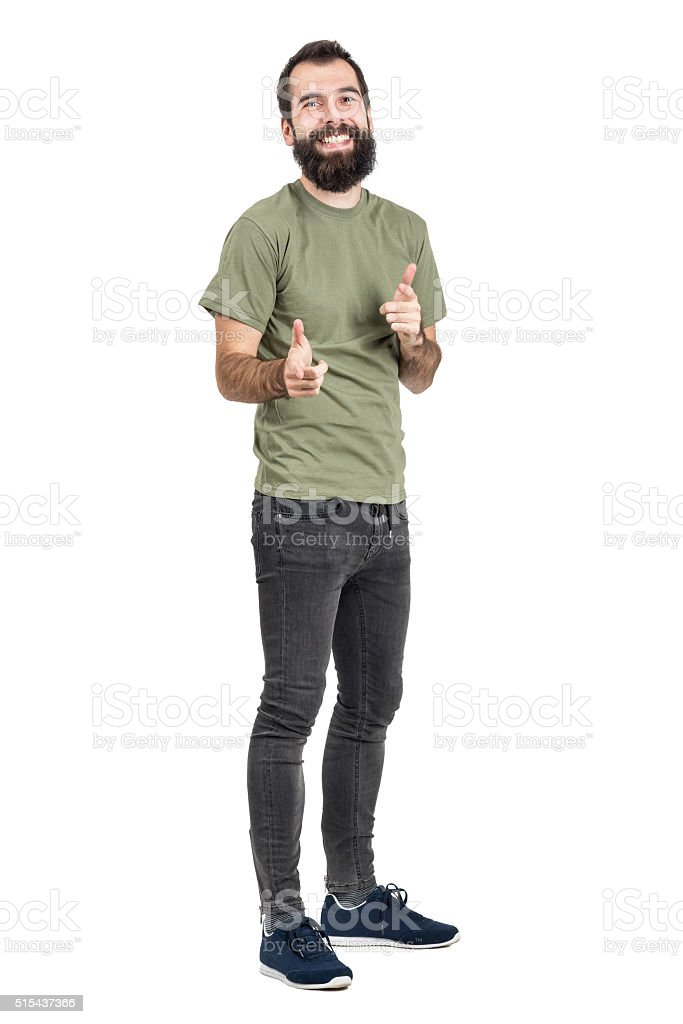 Spontaneously laughing man in green t-shirt pointing fingers at camera stock photo