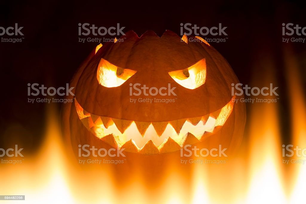 Spooky carved halloween pumpkin in hot burning hell fire flames stock photo