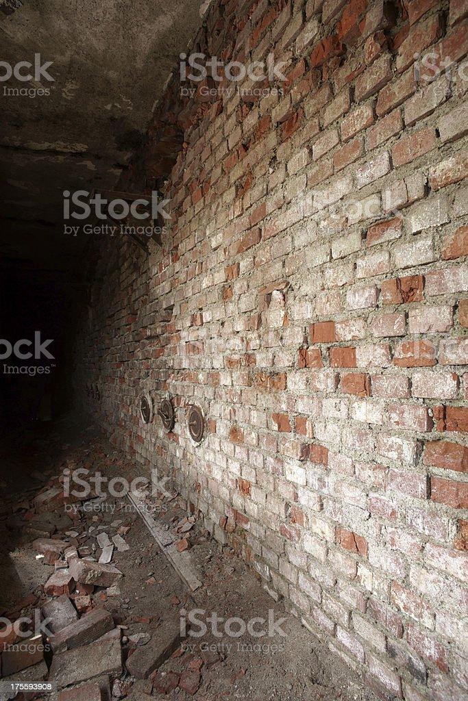 Spooky corridor ending in darkness -  vertical stock photo