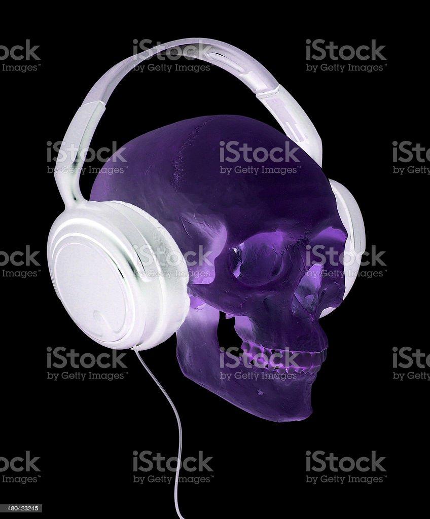 spooky cranium with headphones stock photo