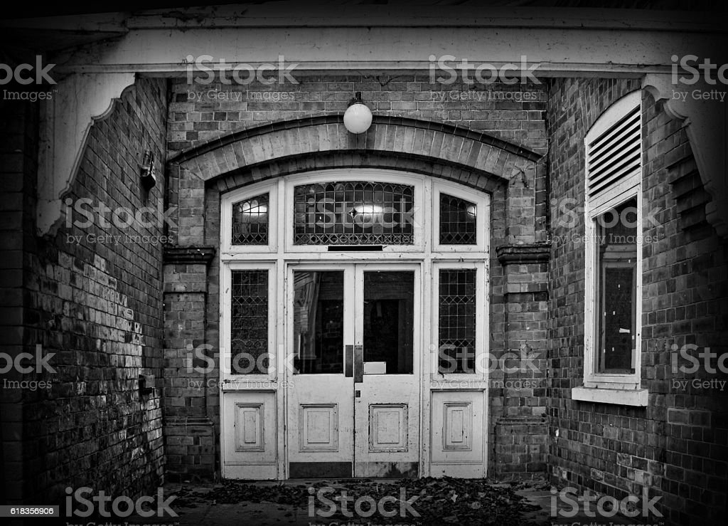 Spooky derelict door in old building - Black and white stock photo