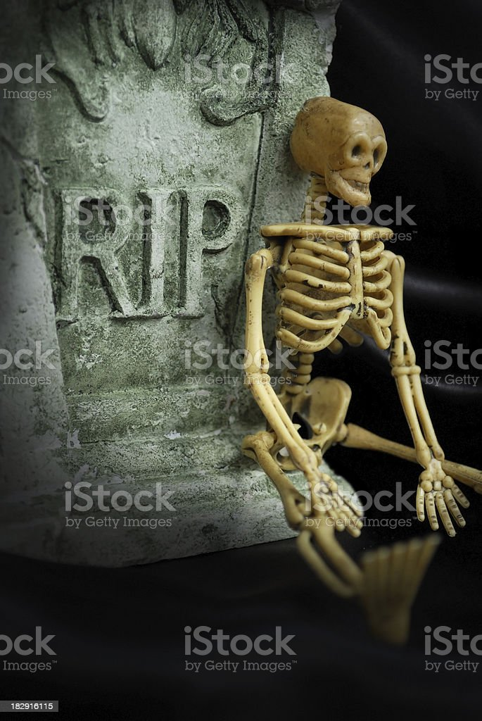 Spooky Halloween Skeleton Sits on a Tombstone with R.I.P. stock photo