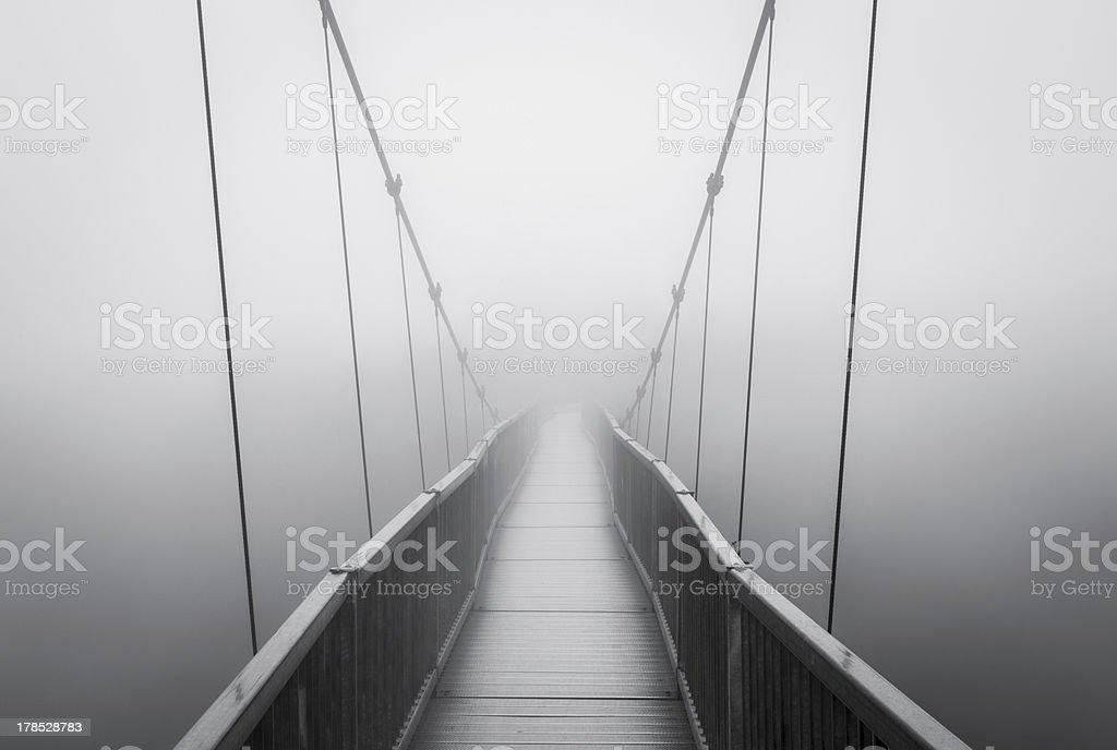 Spooky Heavy Fog on Suspension Bridge Vanishing into Creepy Unknown stock photo