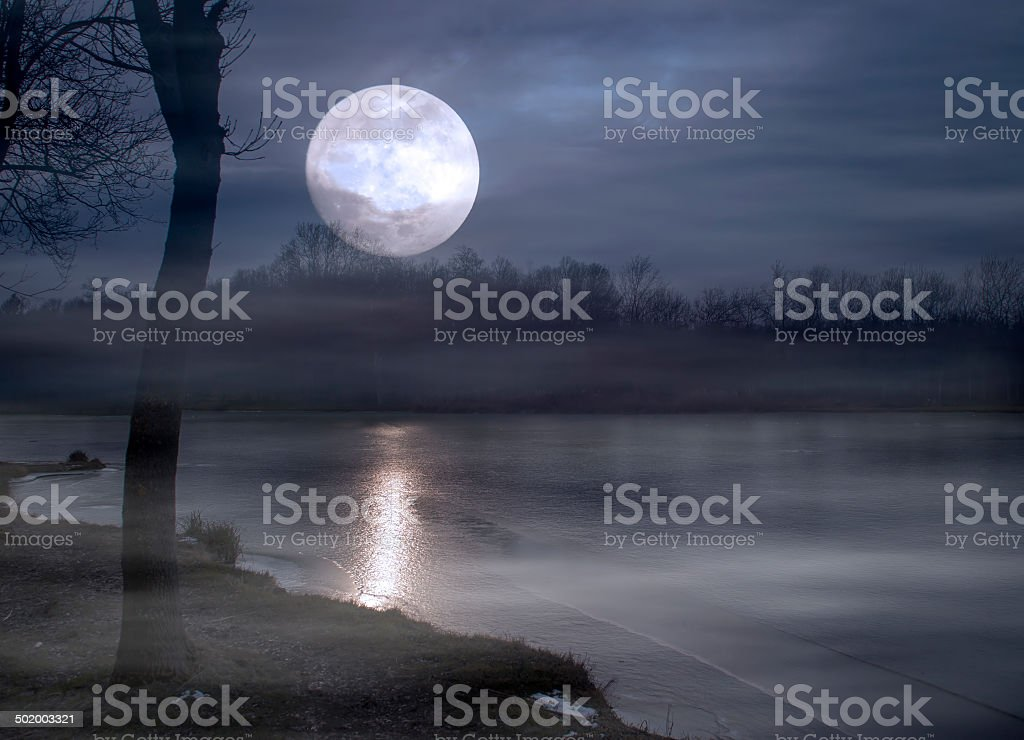 Spooky moonrise over lake stock photo