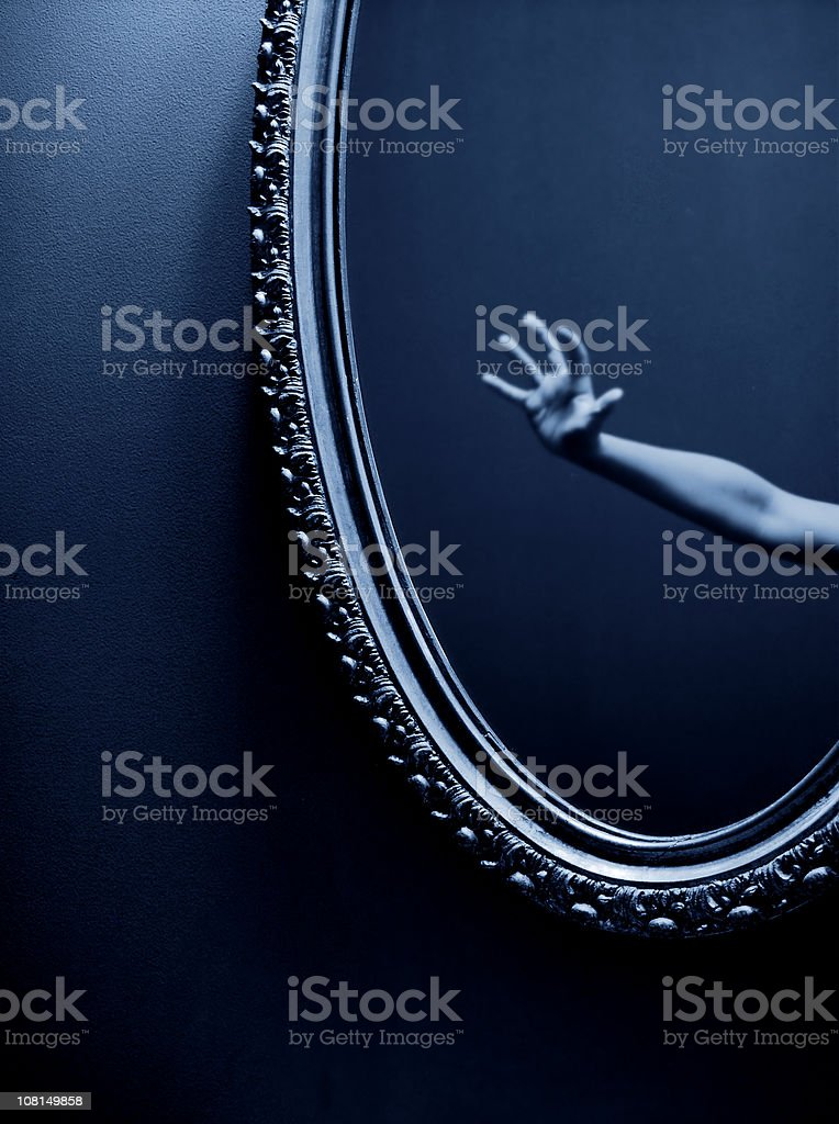Spooky Reflection of Hand Reaching Out in Mirror, royalty-free stock photo