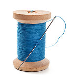 A spool of blue thread with a needle in it