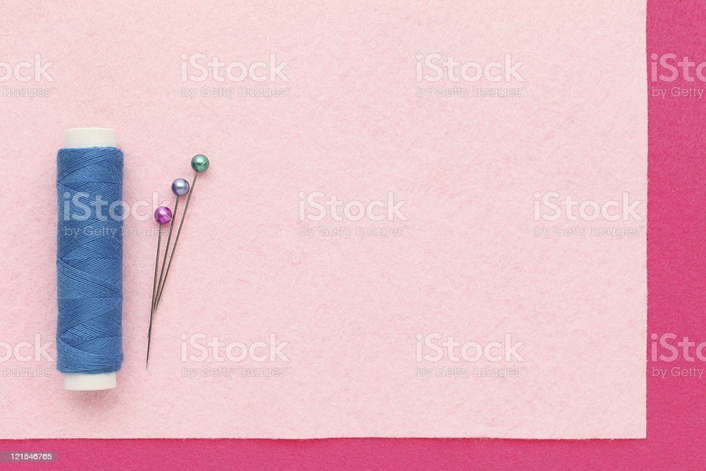 Spool of thread and pins on cloth royalty-free stock photo