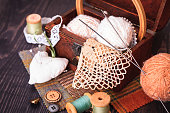 Spool of thread, thimble and a box with needlework