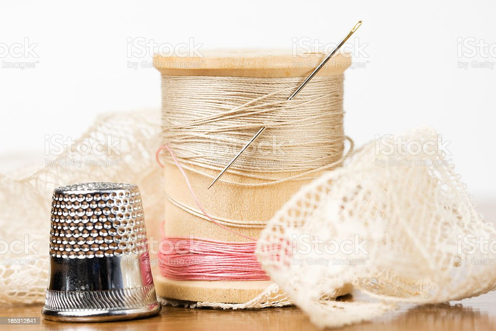 Spool of Thread with Needle, Thimble and Lace royalty-free stock photo