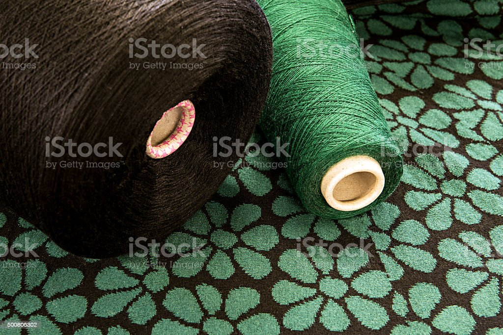 Spools of Brown and Green Thread on Floral Surface stock photo