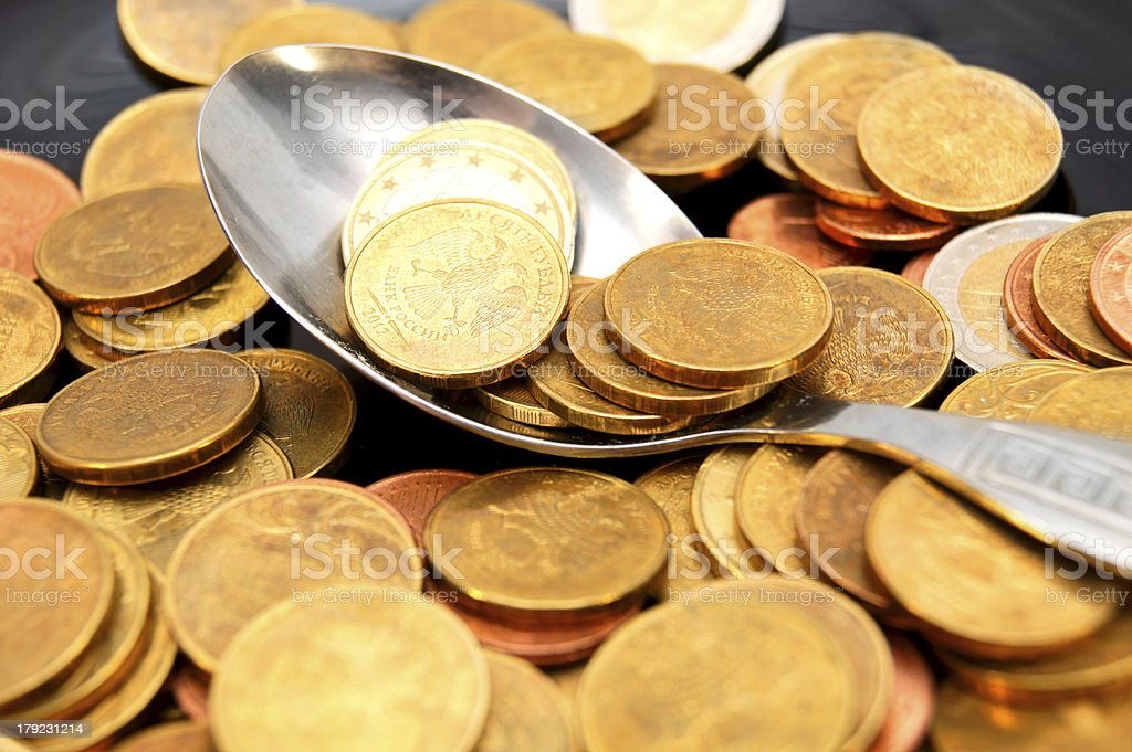 Spoon. A scattering of coins. royalty-free stock photo