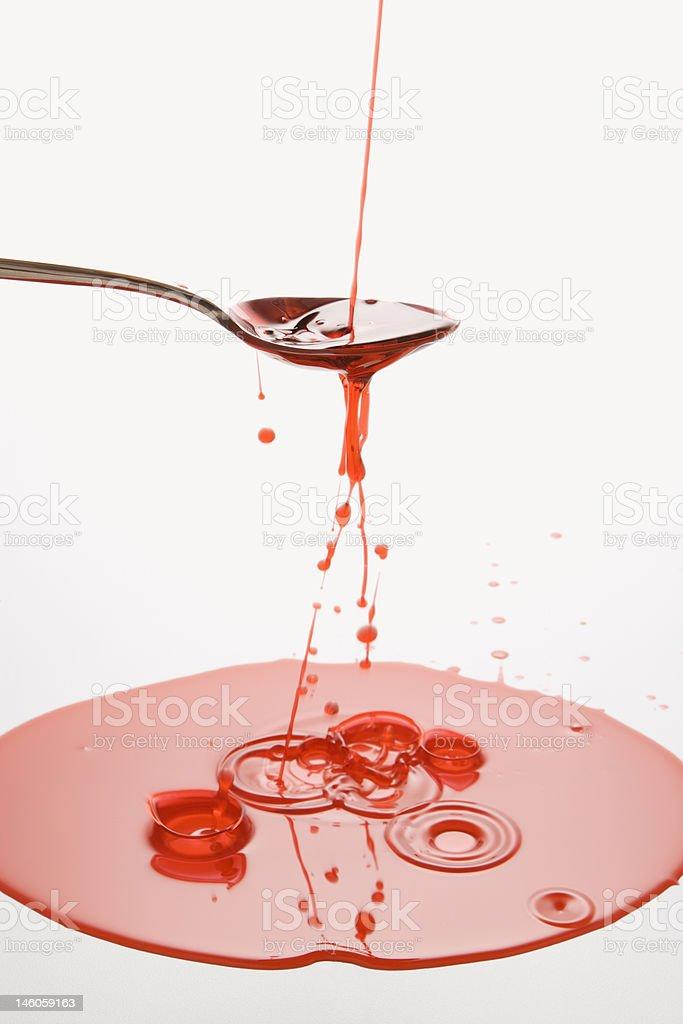Spoon and spilt liquid royalty-free stock photo