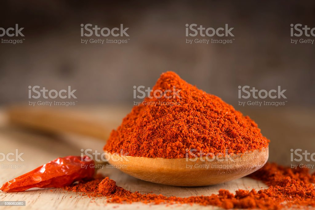 Spoon filled with red hot paprika powder stock photo