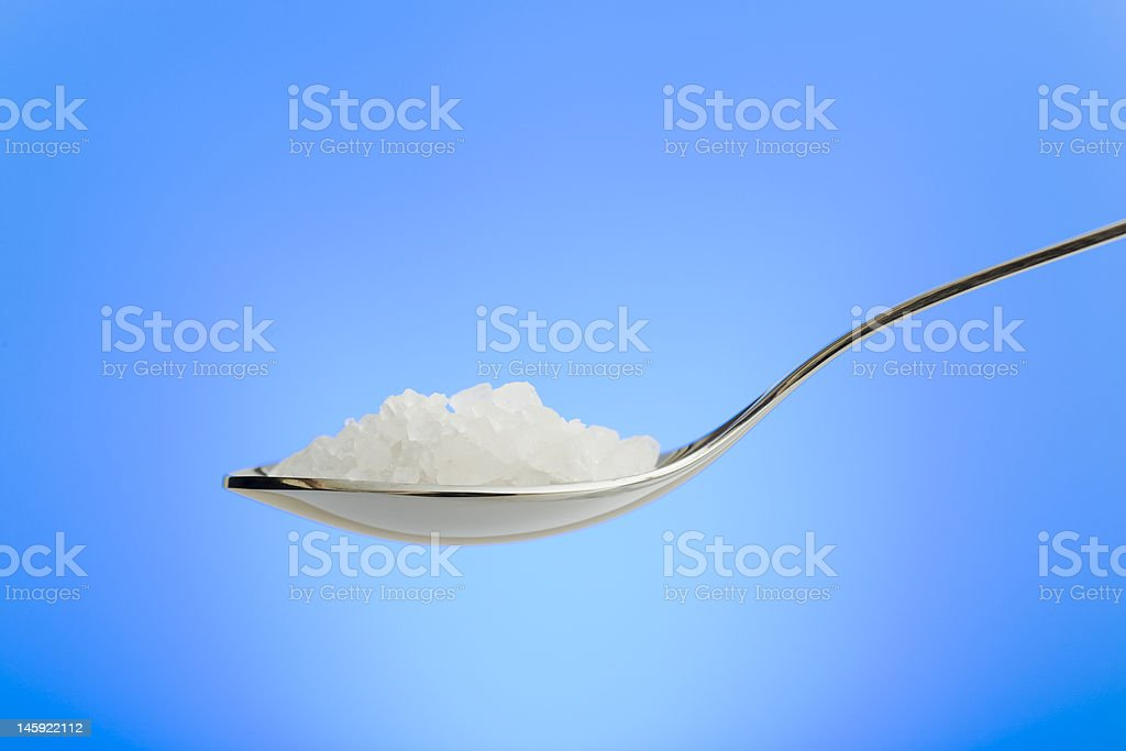 Spoon filled with sea salt royalty-free stock photo