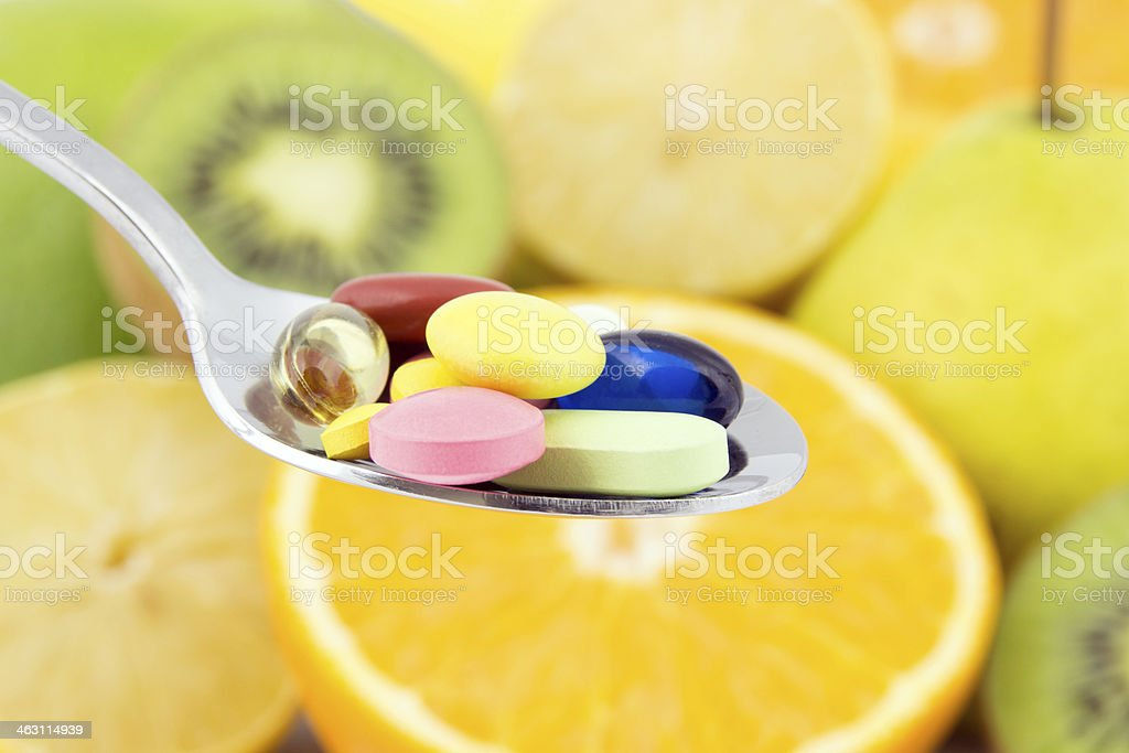 Spoon full of colorful pills stock photo