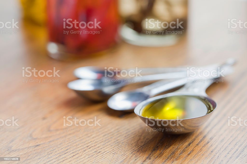 A spoon full of olive oil on a table stock photo