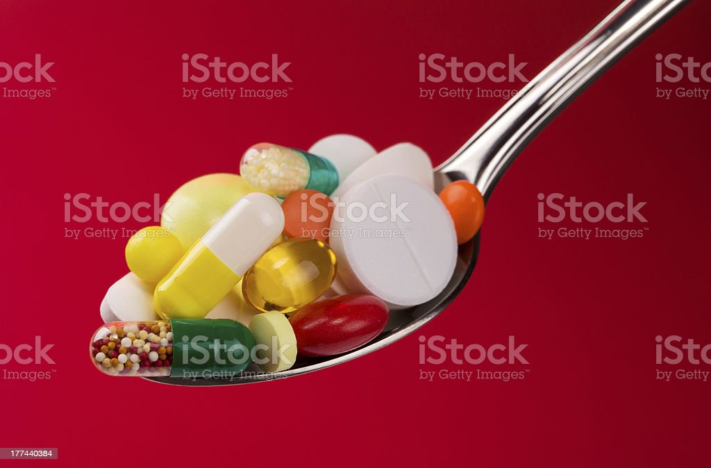 Spoon full of various pills royalty-free stock photo