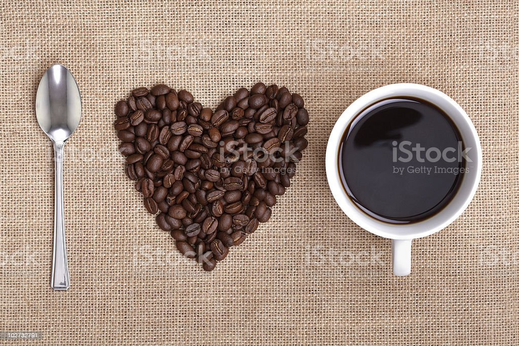 Spoon, heart-shaped pile of coffee beans, and cup of coffee royalty-free stock photo