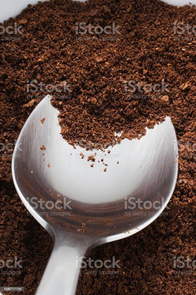 Spoon inside of ground coffee stock photo