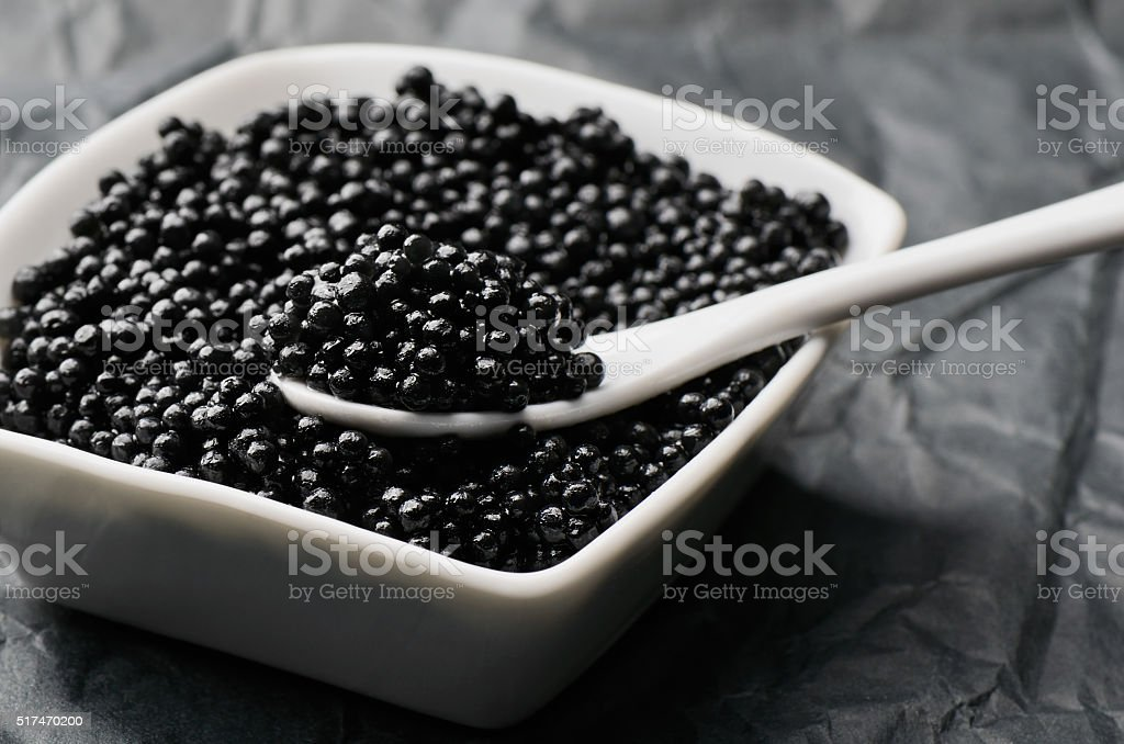 spoon of black caviar in a white bowl stock photo